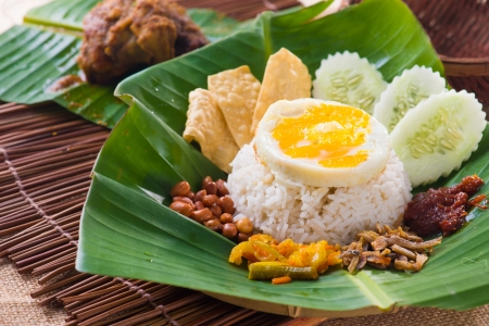 indonesian food: nasi lemak, a traditional malay curry paste rice dish served on a banana leaf