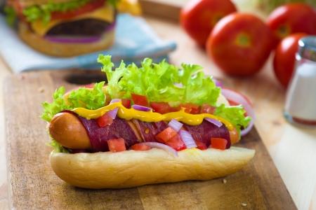 perro caliente y el tocino servido con tomate mostaza y un montón de fondos
