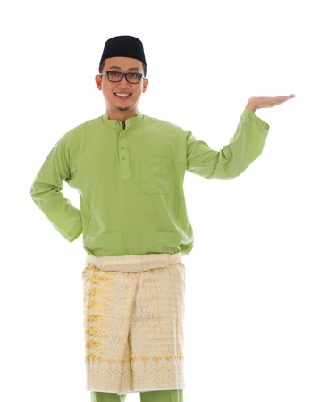 Traditonal Malay man with welcome gesture during ramadan isolated white background photo