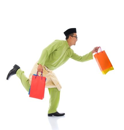 Traditional Malay male shopping and jumping in joy during hari raya ramadan festival photo