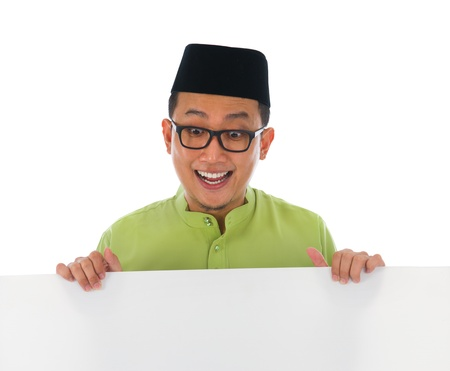 aidilfitri: malay male with blank card during hari raya Eid al-Fitr celebration