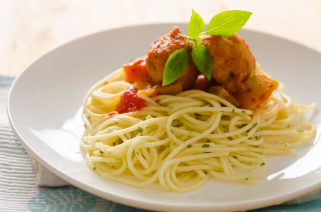 plate of spaghetti with meatballs in tomato marinara sauce and ingredients on a wooden table   photo