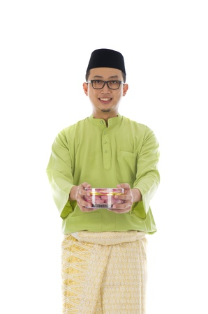 Traditional Malay male with biscuit during hari raya photo