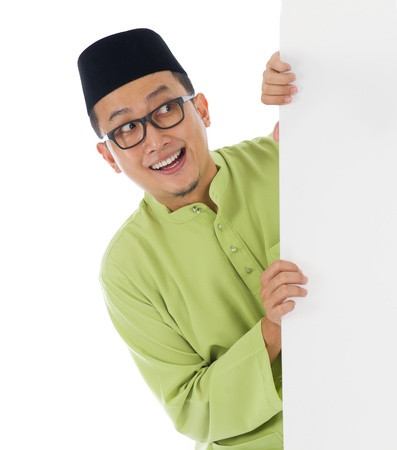 aidilfitri: malay male with blank card during hari raya Eid al-Fitr celebration   Stock Photo