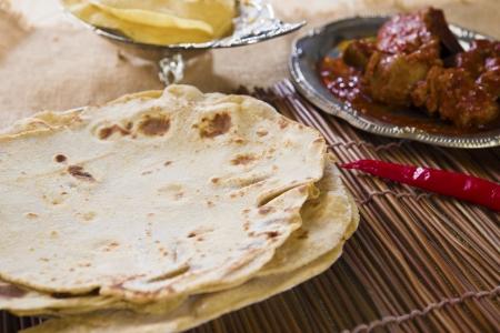 Chapatti roti, curry chicken, biryani rice, salad, masala milk tea and papadom  Indian food on dining table  photo