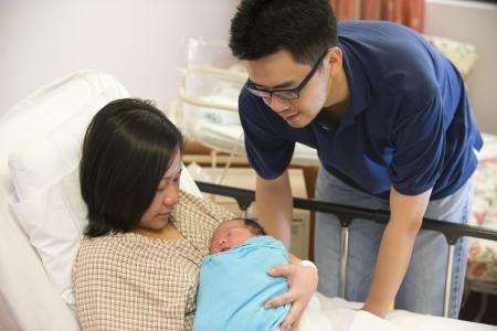 アジアの中国の生まれたばかりの赤ちゃん女の子と病院のパパ 写真素材