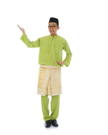 Traditonal Malay man with welcome gesture during ramadan isolated white background   Stock Photo