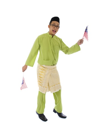 malay village: malay male jumping with malaysian flags wearning traditional clothes Stock Photo