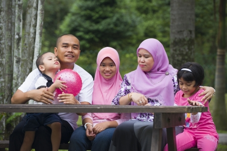 malay family having fun in the green outdoor park   photo