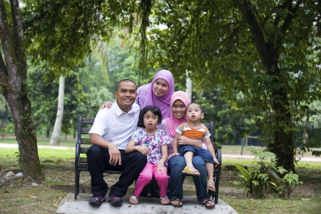 malay family sitting and having fun in the park   photo
