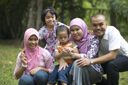 enjoyable: malay muslim family having fun in the park   Stock Photo