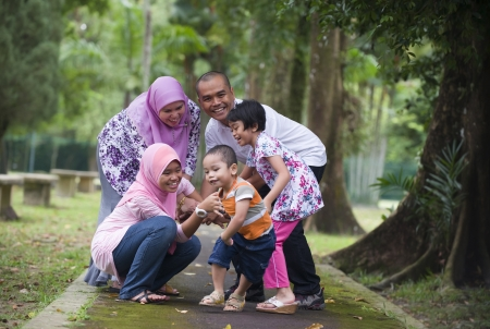 malay: malay muslim family having fun playing in the park   Stock Photo