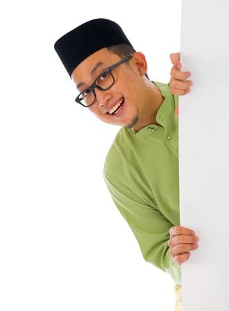 aidilfitri: malay male with blank card during hari raya Eid al-Fitr aidilfitri celebration