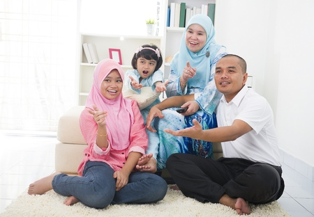 malay family watching television enjoying quality time photo