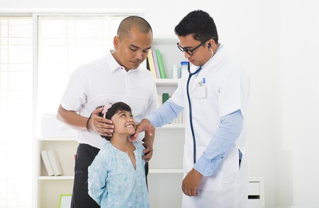check up: malay father and sick daugther visiting the doctor Stock Photo
