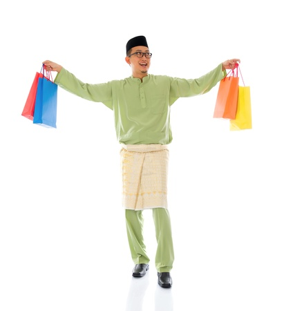 Traditional Malay male shopping and jumping in joy during hari raya ramadan aidilfitri festival   photo