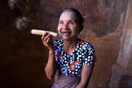 smoking a cigar: Old Asian woman smoking tobacco. Bagan, Myanmar.   Stock Photo