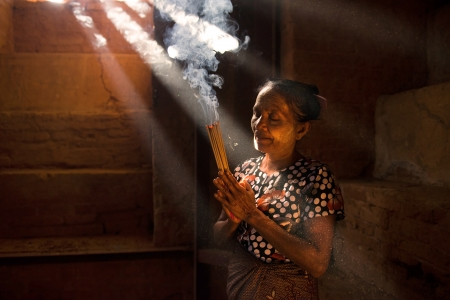 burmese: Traditional Old Asian woman praying with incense sticks inside a temple of bagan Myanmar