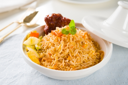 Biryani rice or briyani rice, curry chicken and salad, traditional indian food on dining table.   Stock Photo