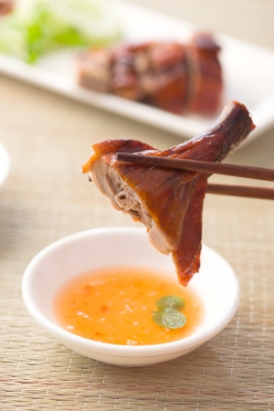 chopstick holding chinese roast duck served with soya sauce and chilli