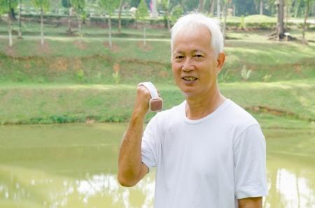 dumb bells: Senior man using dumbells on outdoor