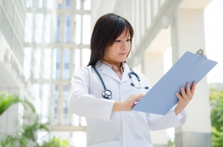 Southeast Asian medical student. Young medical doctor woman standing on hospital background.   photo