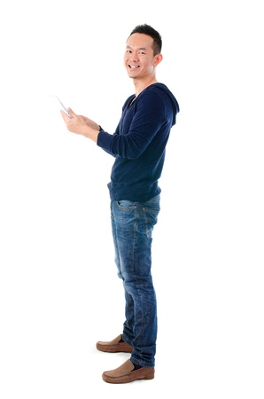 Fullbody Asian man using tablet computer standing over white background   photo