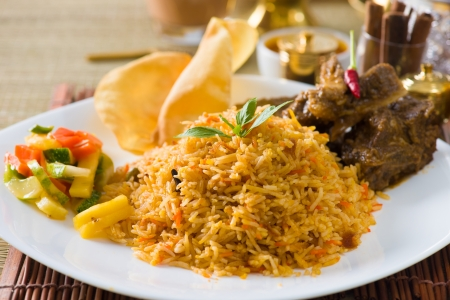 biryani: Biryani mutton rice papadam with traditional background