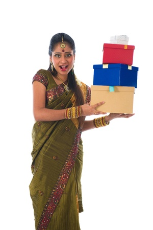Portrait of a woman in traditional saree holding gifts and smiling   photo