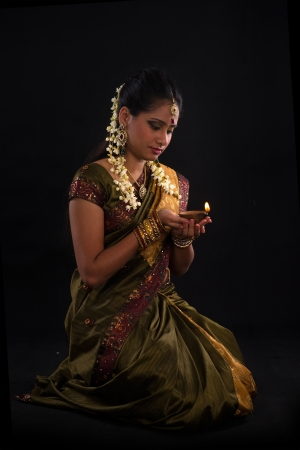 lady with the lamp: traditional indian woman with oil lamp during the celebration of deepawali or diwali
