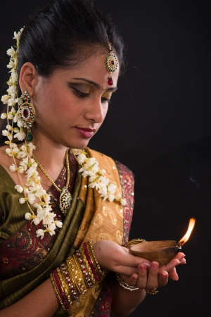 deepawali: traditional indian woman with oil lamp during the celebration of deepawali or diwali