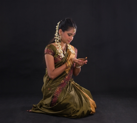 saree: traditional indian woman with oil lamp during the celebration of deepawali or diwali