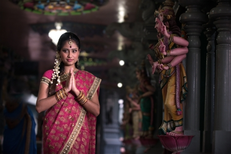 traditional Young indian woman praying in the temple Stock Photo