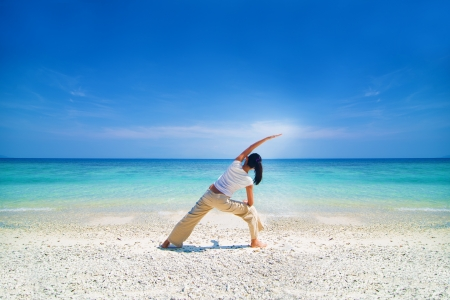 asian female performing yoga on a beach   photo
