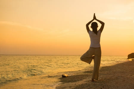 silhouette of a girl performing yoga on beach sunset   Stock Photo