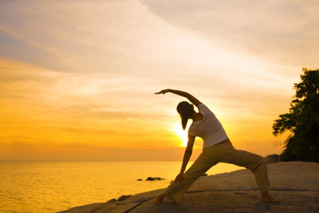 healthy living: silhouette of a girl performing yoga on beach sunset   Stock Photo