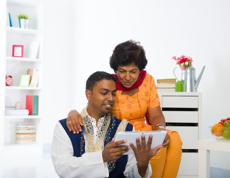indian mother and son enjoying surfing with tablet in the livingroom photo