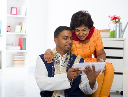 salwar: indian mother and son enjoying surfing with tablet in the livingroom