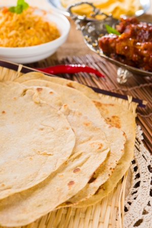 Chapatti roti and Indian food on dining table.   photo
