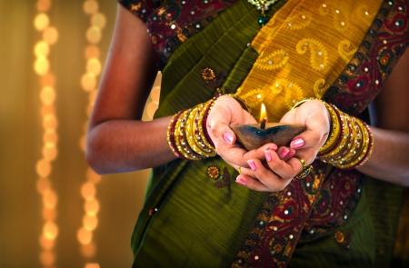 candil: foto deepavali con l�mpara de aceite que sostiene femenina durante el festival de la luz Diwali o