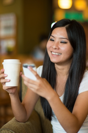 asian girl lifestyle on phone while enjoying coffee in cafe photo