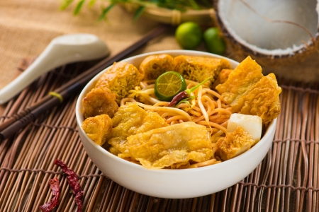 laksa: chopstick and laksa curry noodles with plenty of raw ingredients