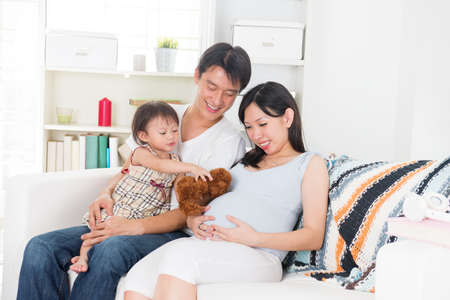 pregnant relaxing on sofa: pregnant mother enjoying quality time with her family