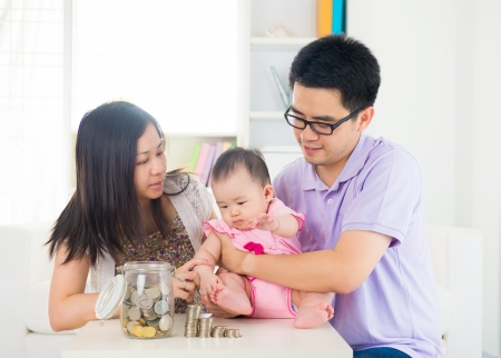 Asian baby putting coins into the glass bottle with help of parents. Money saving education concept. photo