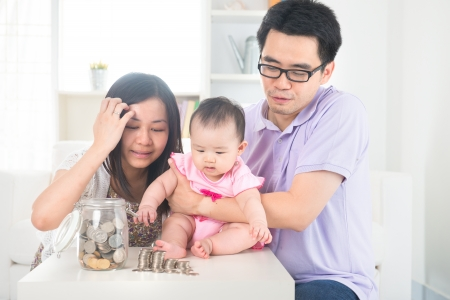 home finance: Asian baby putting coins into the glass bottle with help of parents. Money saving education concept.   Stock Photo