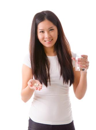 happy asian girl taking supplement pills photo