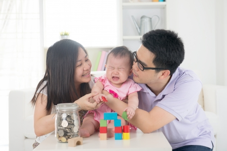 crying asian baby being comforted by chinese parents photo