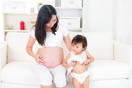 Asian Mutter und ihre kleine Tochter wartet Neugeborenen und zeigt Bauch