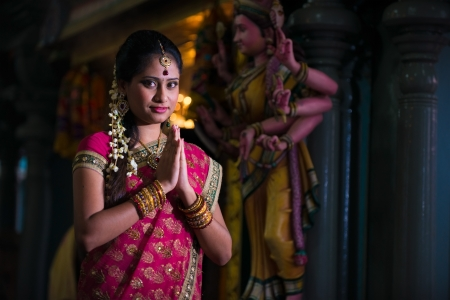 traditional indian female praying in the temple photo