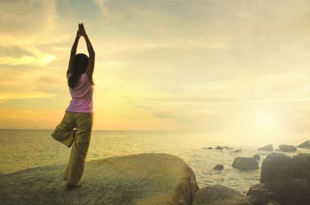 mind body spirit: Silhouette young woman practicing yoga on the beach at sunset.